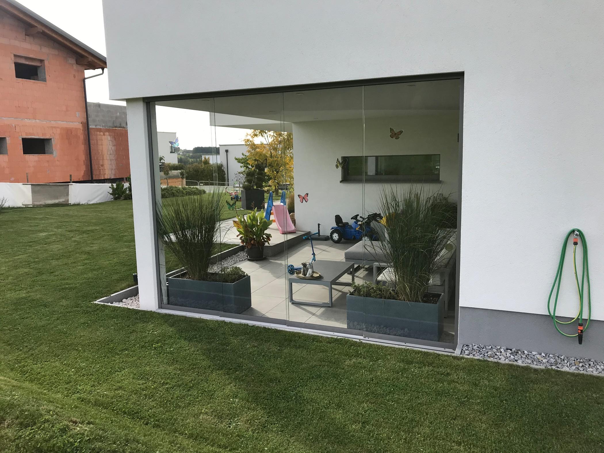 Glasschiebewand für Terrasse als Windschutz in Oberösterreich