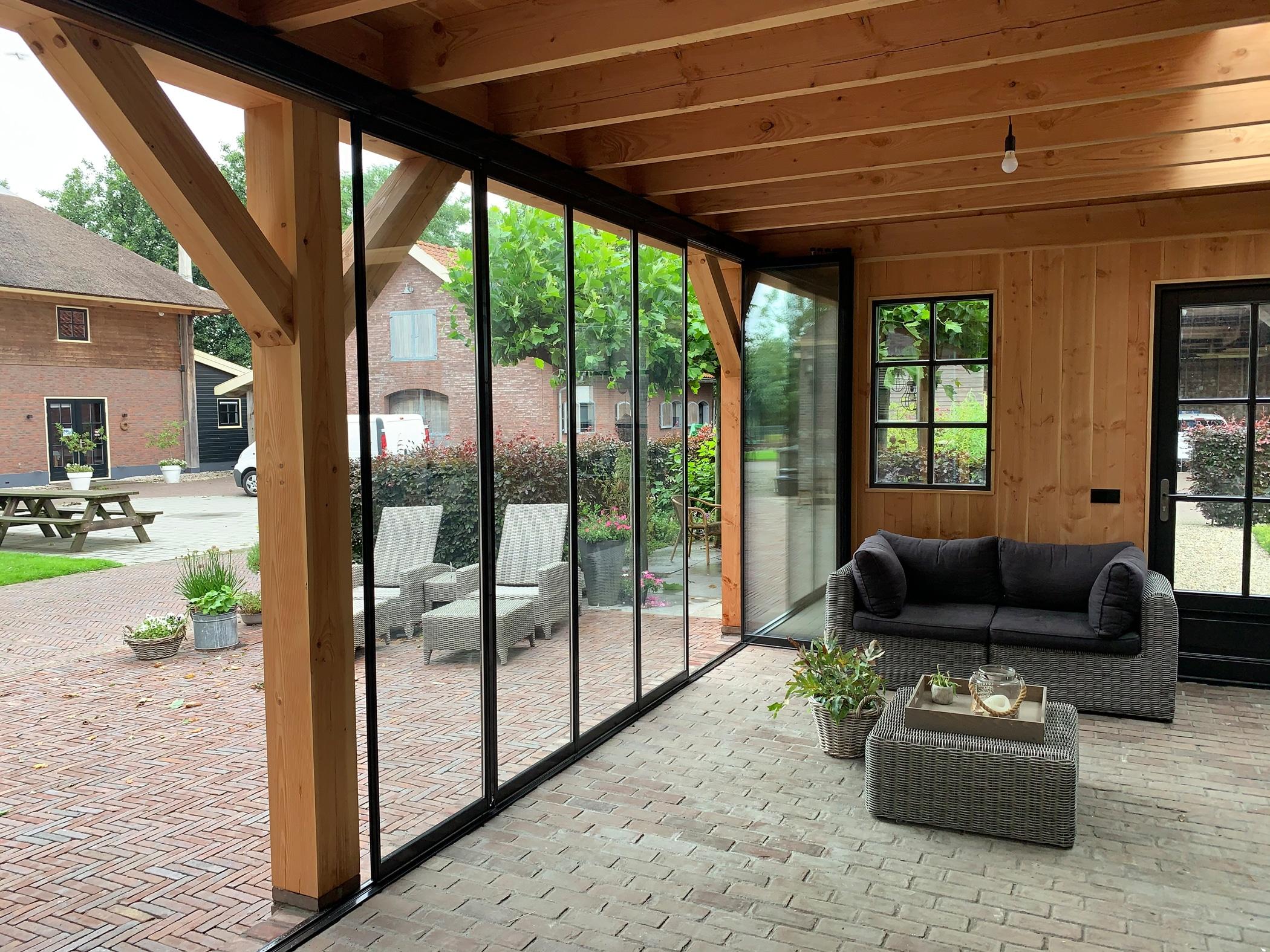 Nachträgliche Verglasung der Terrassenüberdachung mit maßgefertigten Schiebe-Dreh-Systemen