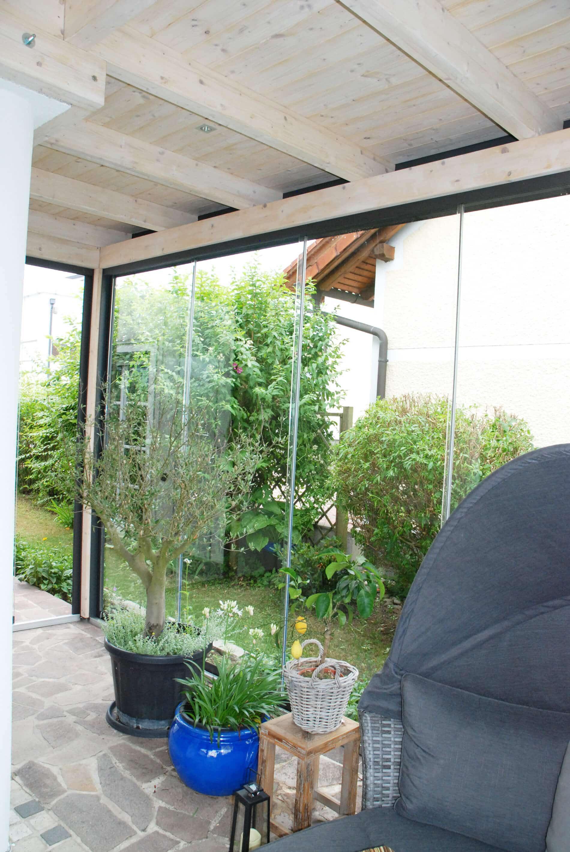 Wintergarten mit Glasschiebewänden als Windschutz